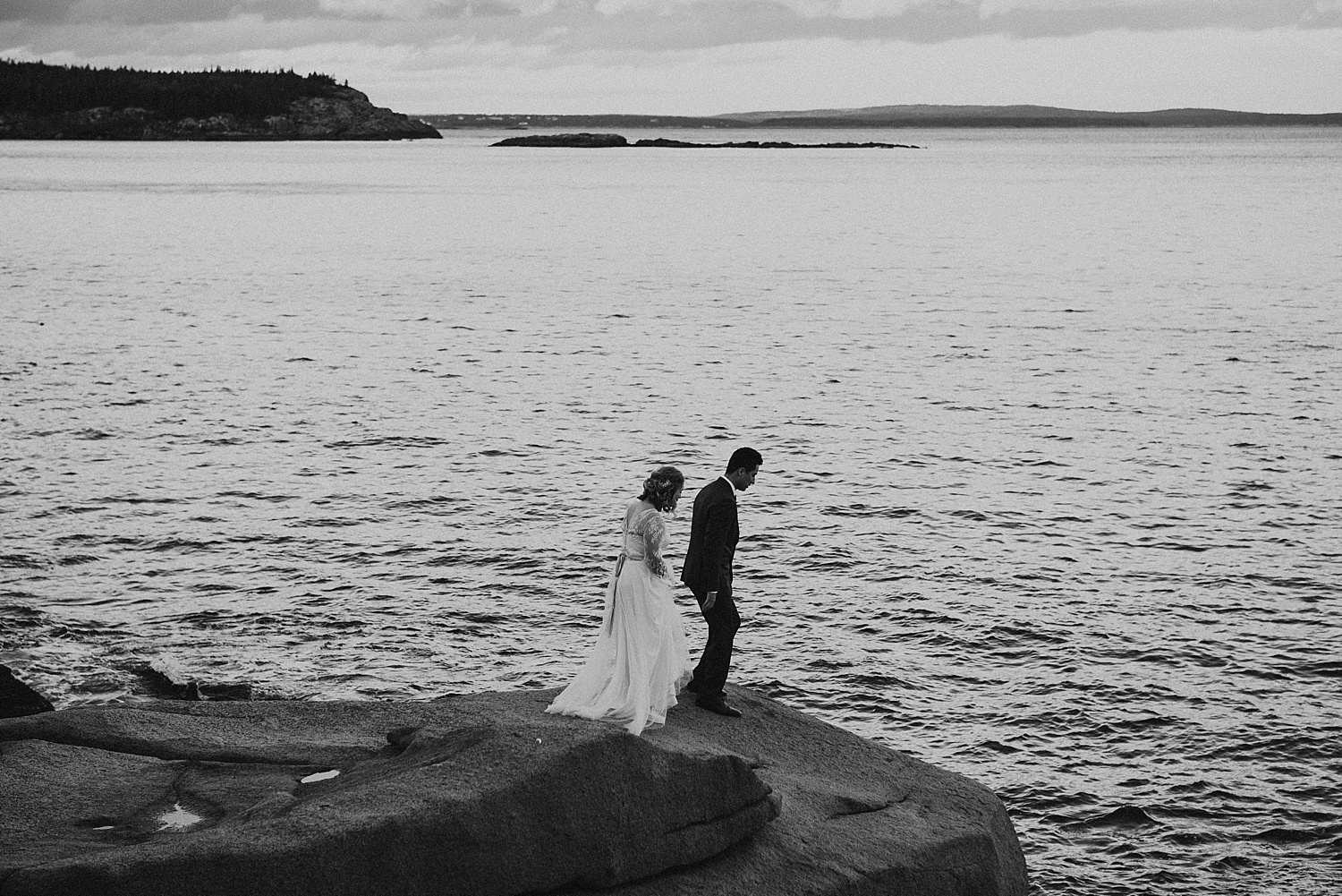 bride and groom walking on sea cliffs
