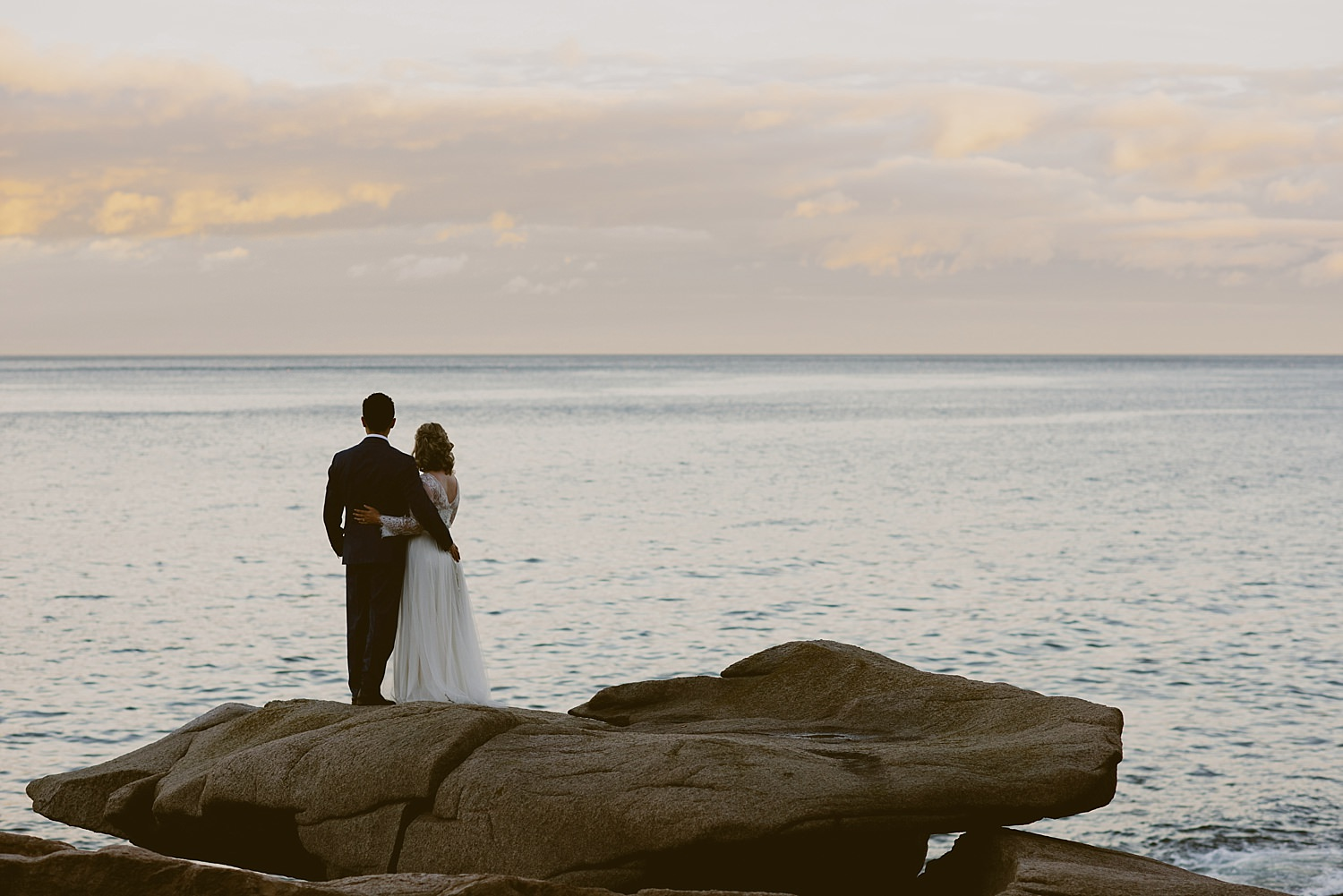 bride and groom looking at the ocean together