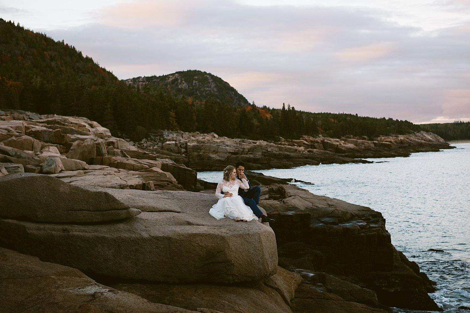 bride and groom sitting on sea cliffs
