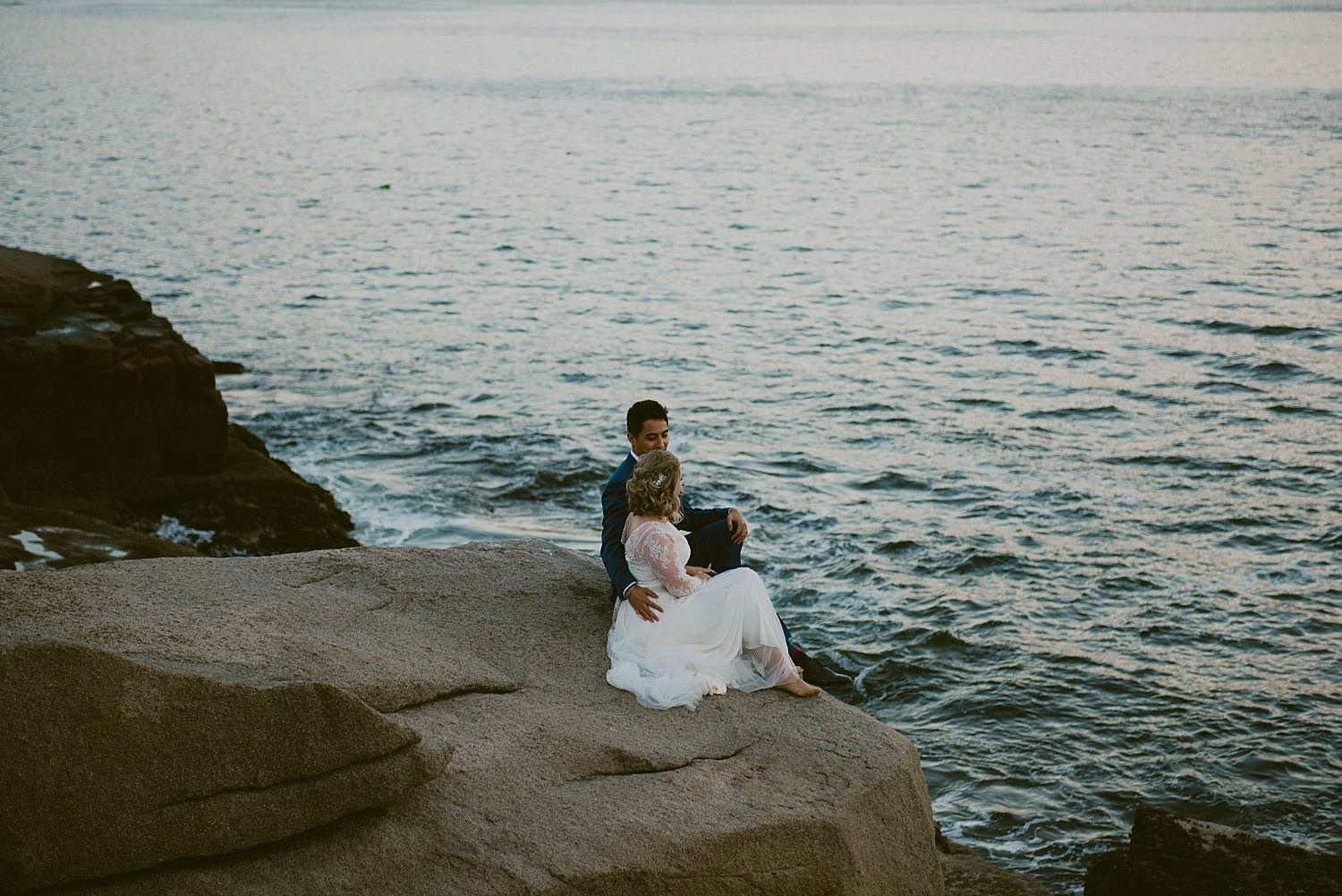 bride and groom snuggled on the rocks