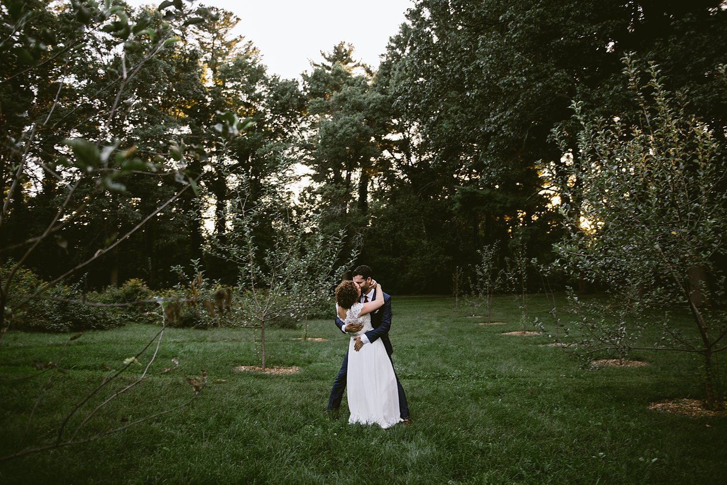 Groom kissing bride in field