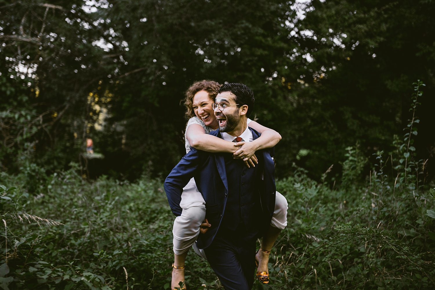 Bride riding piggy back on groom