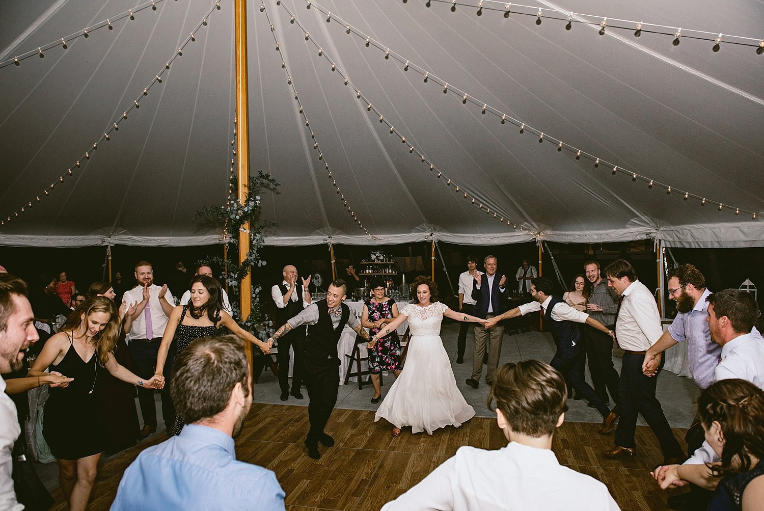 Bride and groom dancing with family