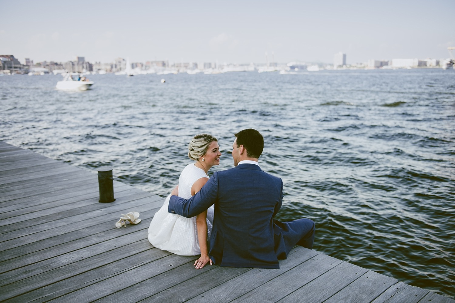 bride and groom sitting on the pier