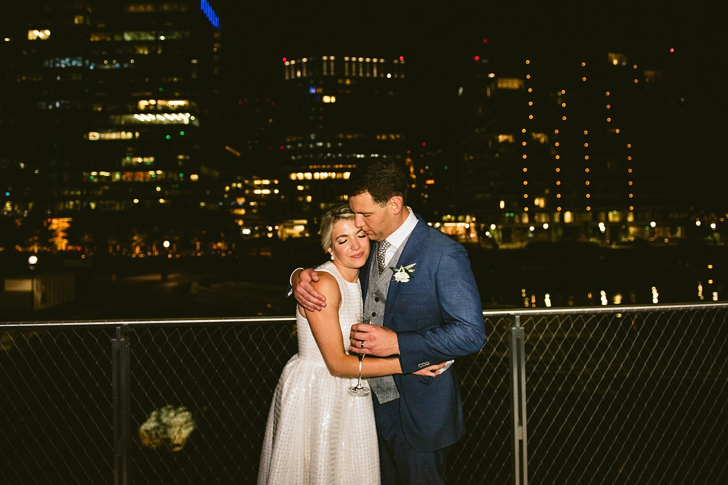 bride and groom with city lights at night