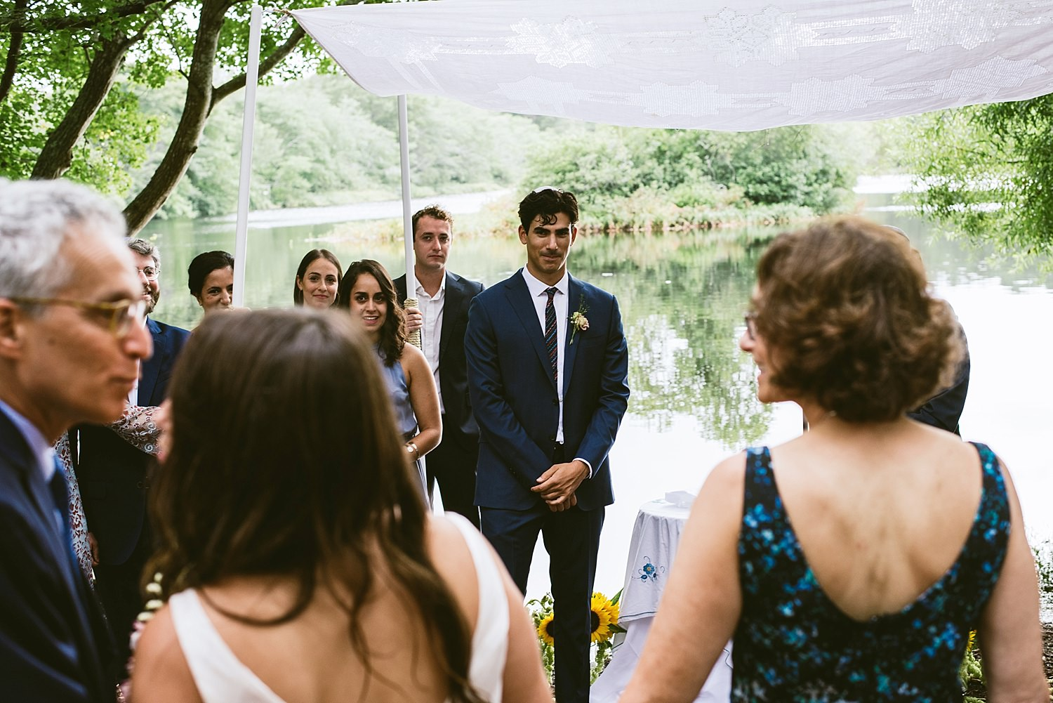 Grooms face as bride walks down the isle
