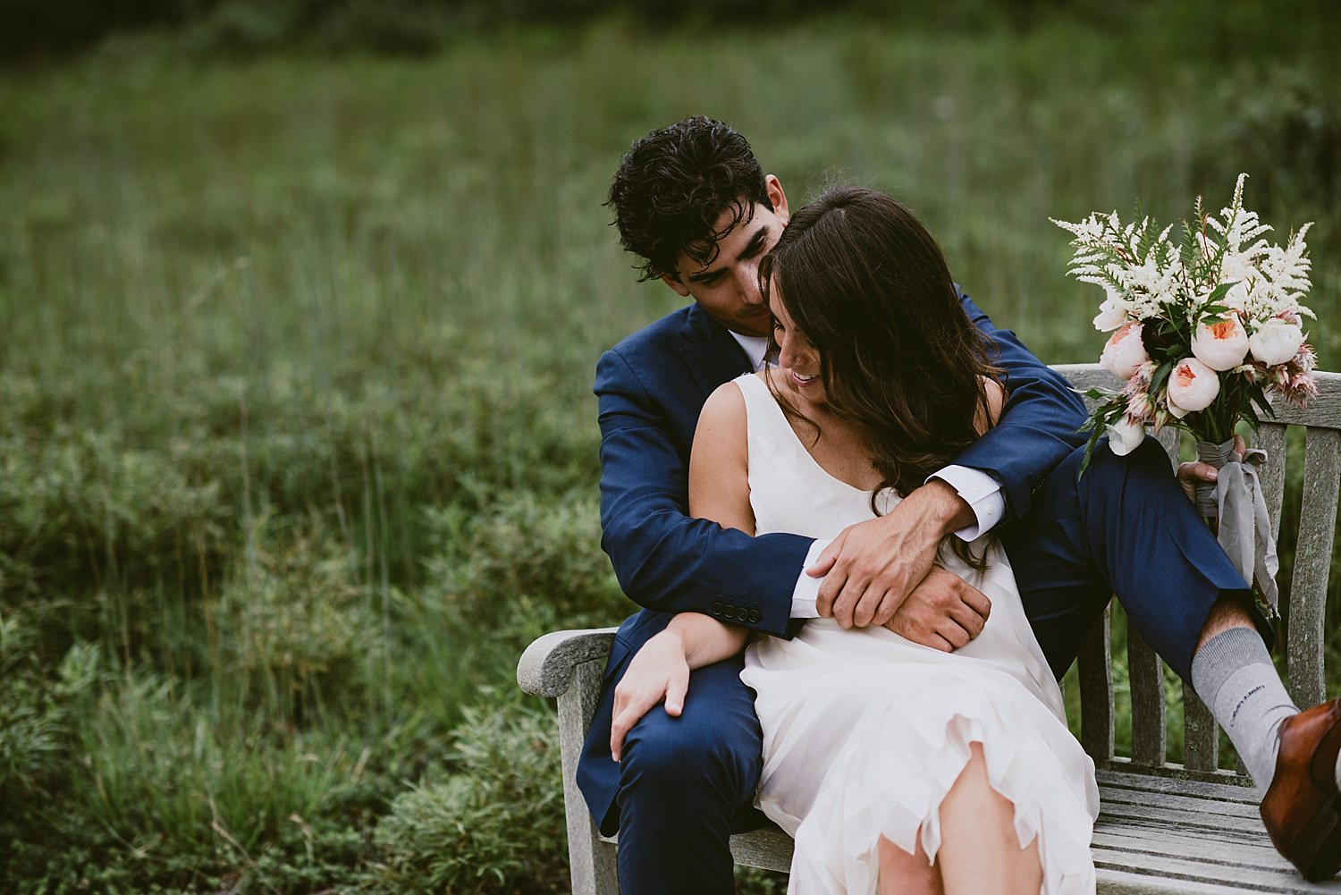 groom embracing bride on bench
