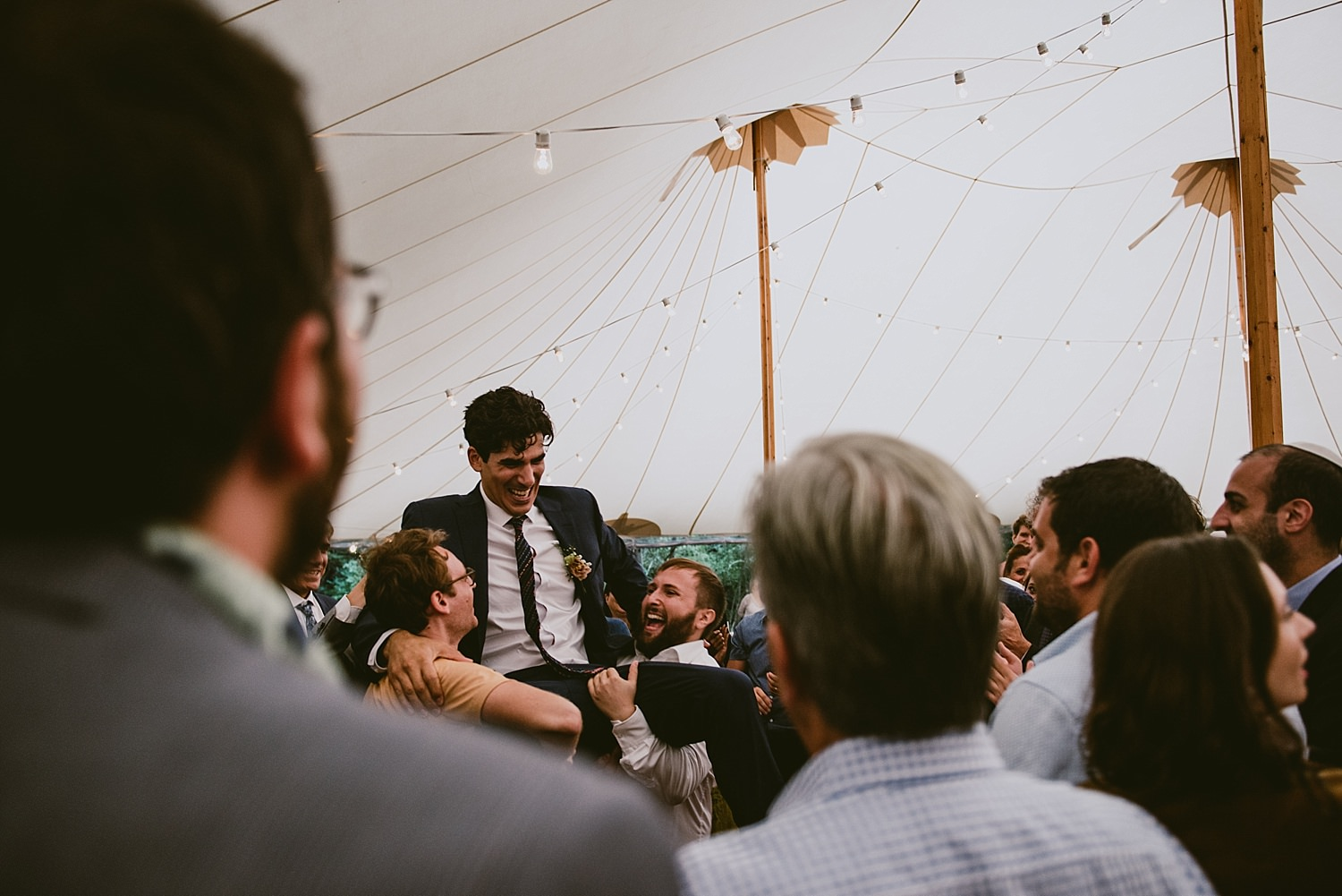 grooms men hoisting groom on shoulders