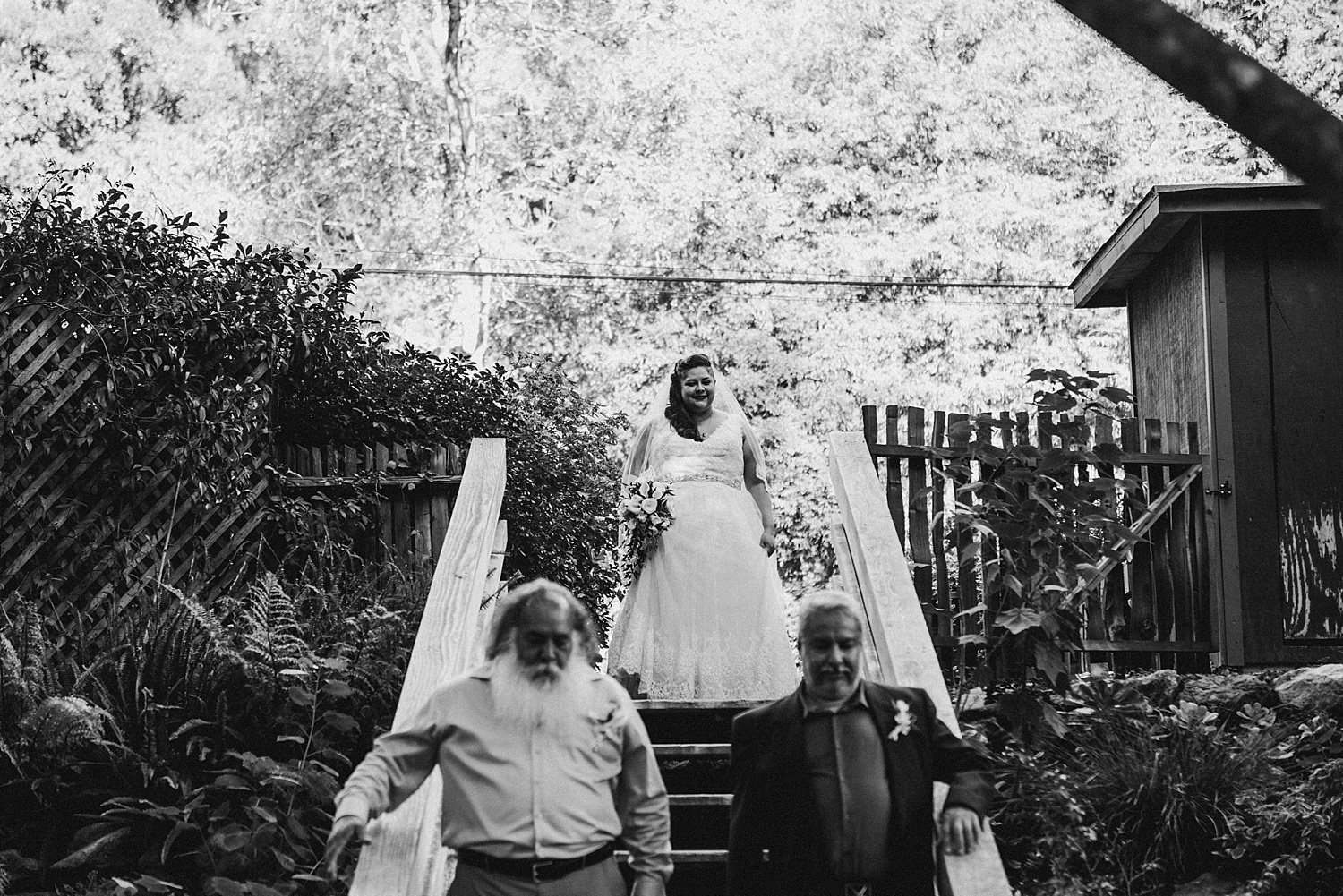 Bride walking down the isle with her two dads