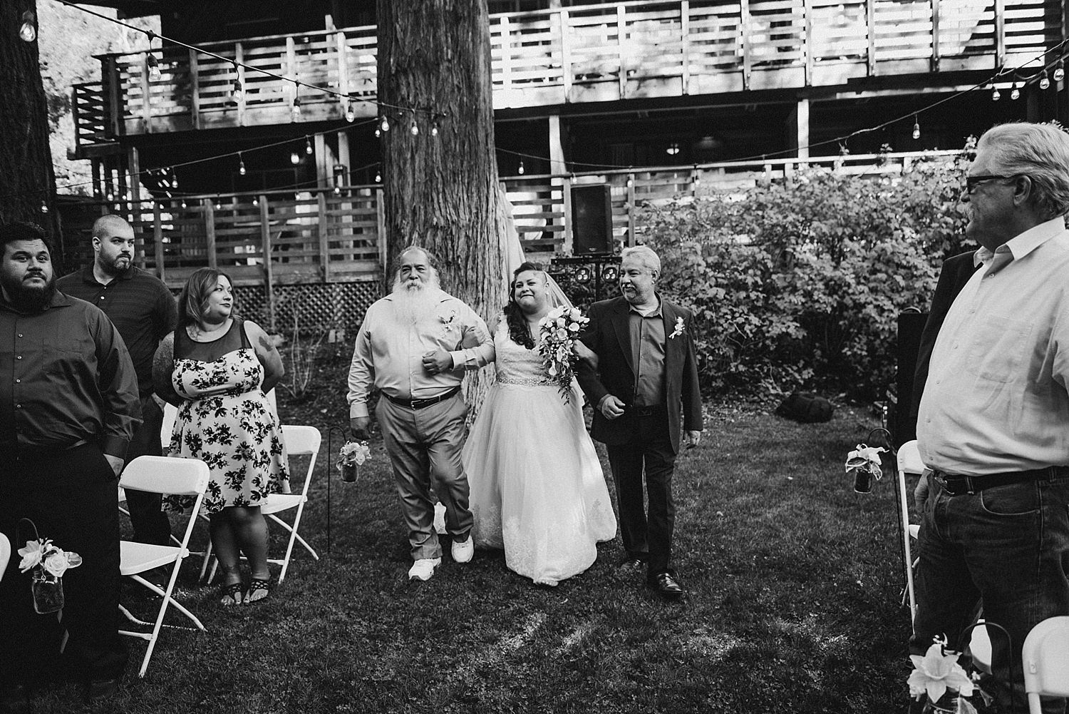 bride and her two dads walking down the isle
