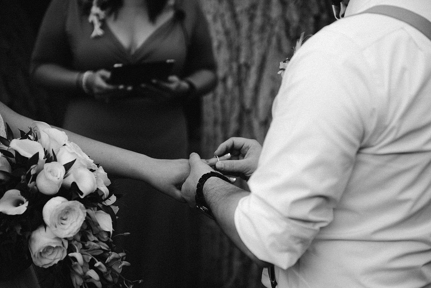 groom putting the ring on the bride