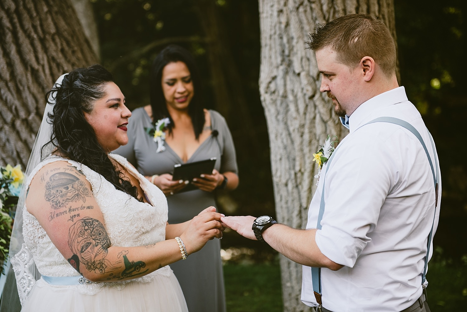bride putting the ring on the groom