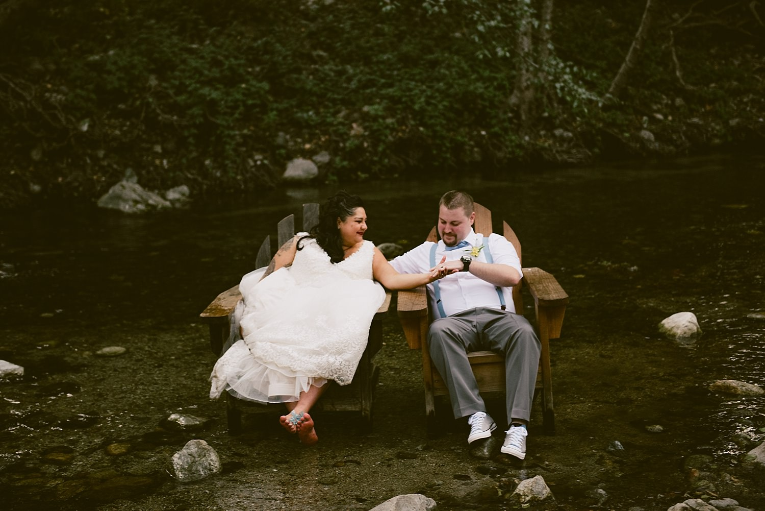 bride and groom sitting in chairs at the river