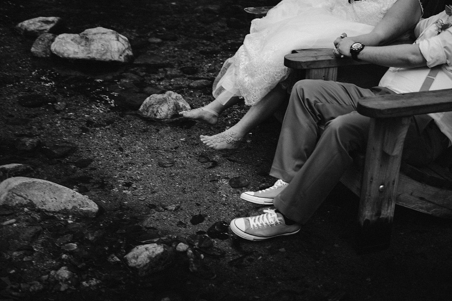 bride and groom with feet in the river