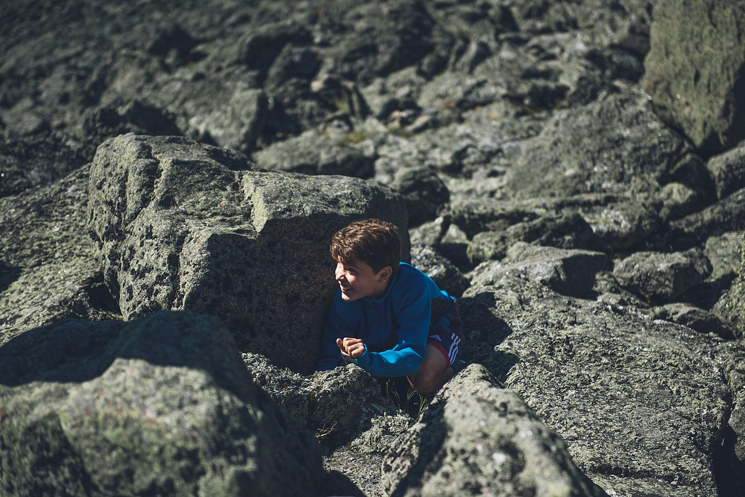 little kid hiding in the rocks