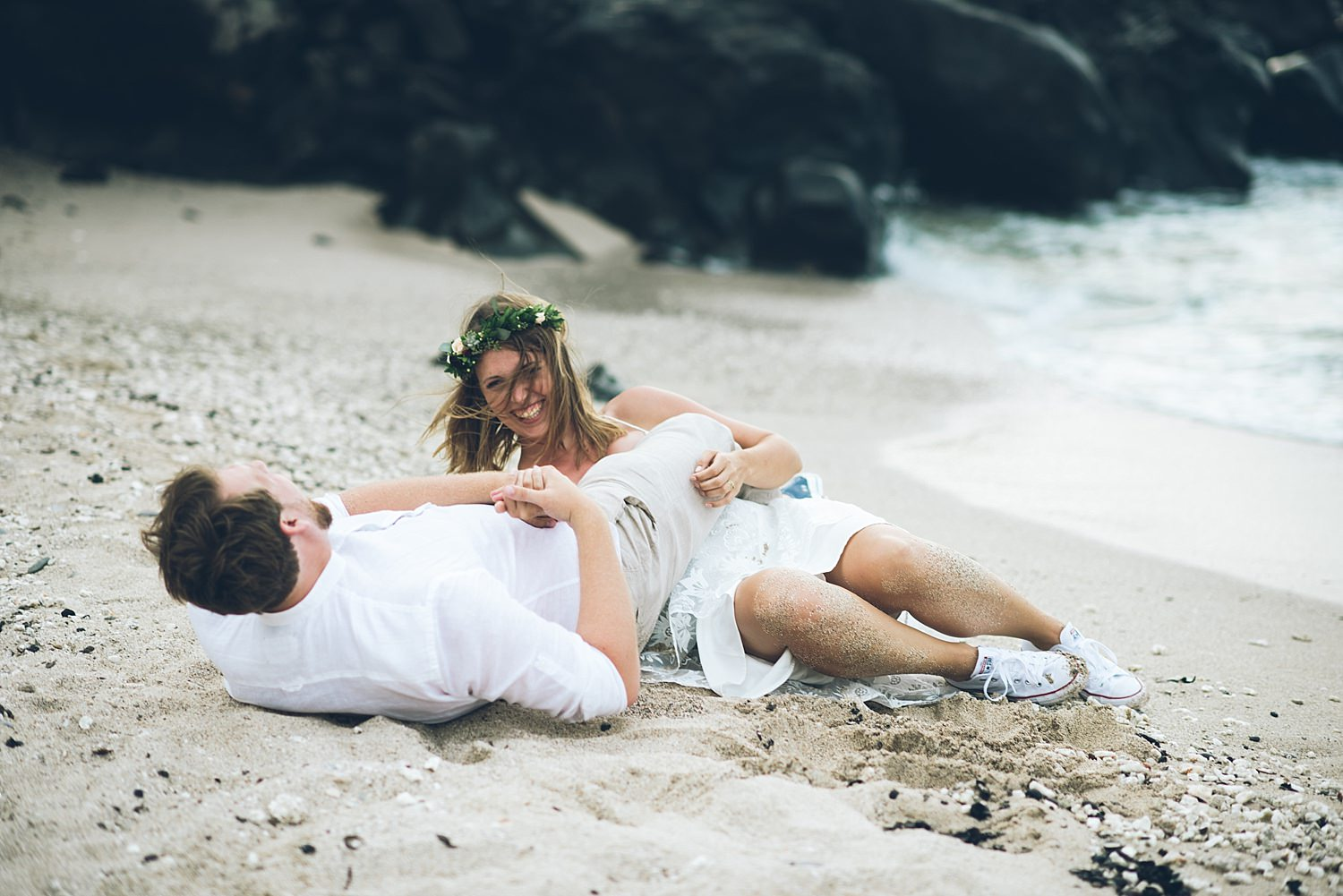 bride and groom playing in the sand