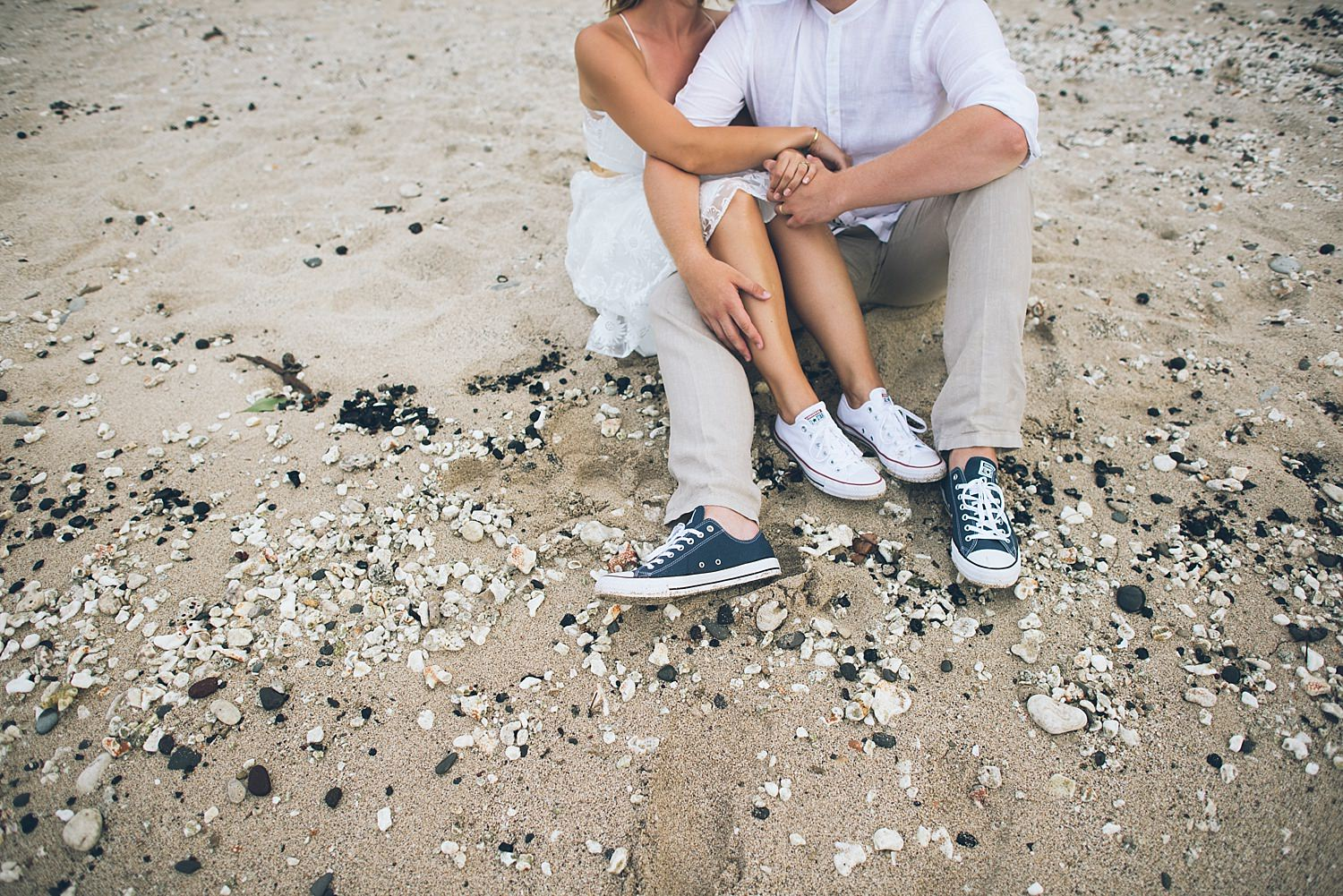 bride and grooms converse in the sand