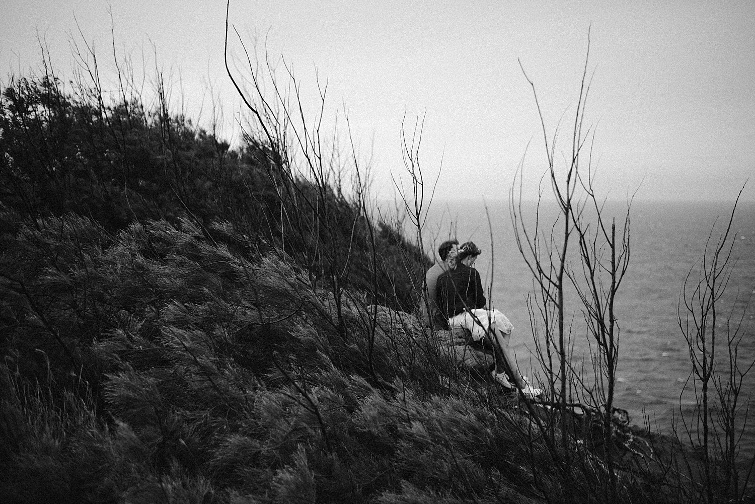 bride and groom sitting on the cliffs