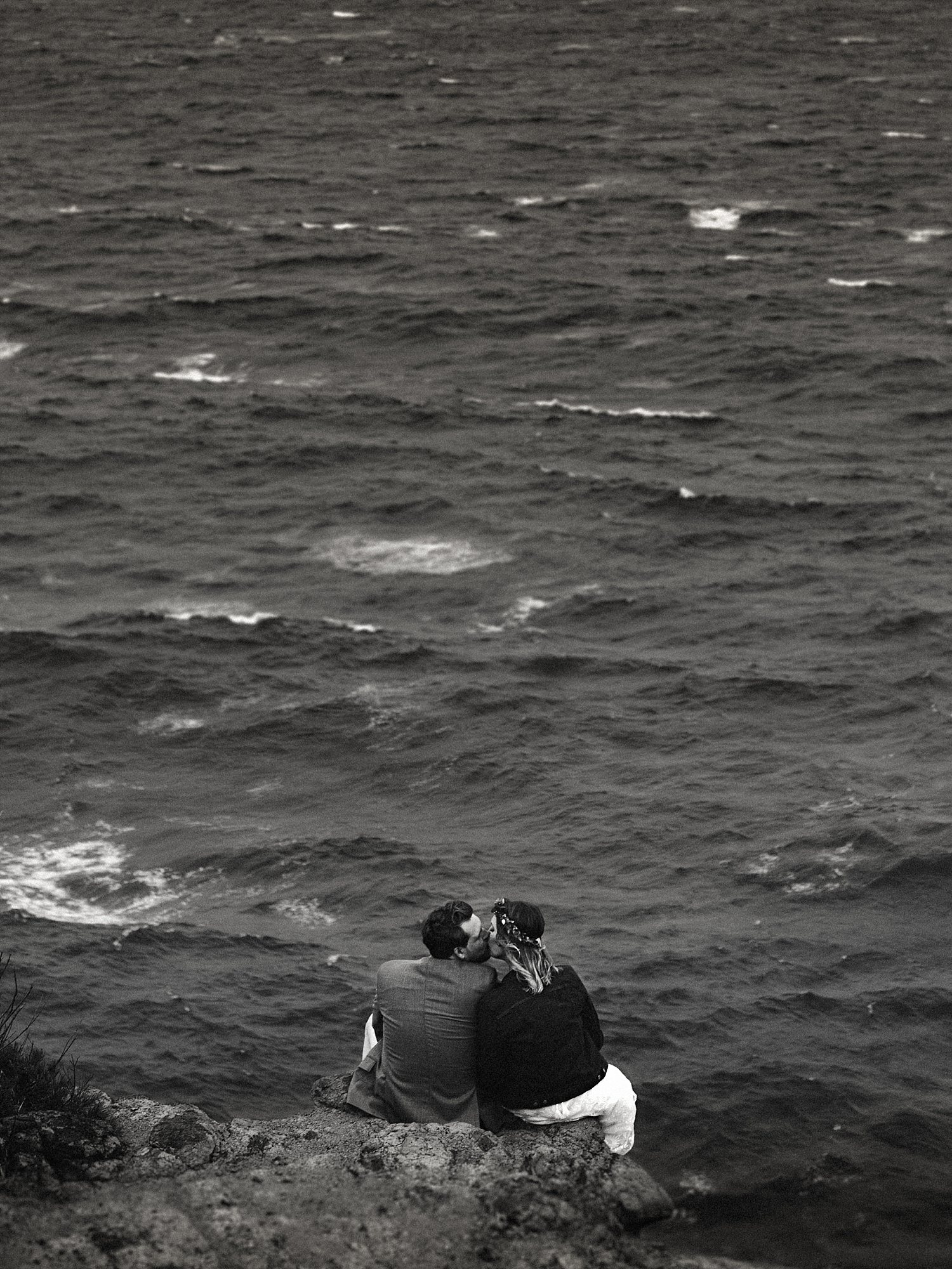 bride and groom sitting on a cliff kissing