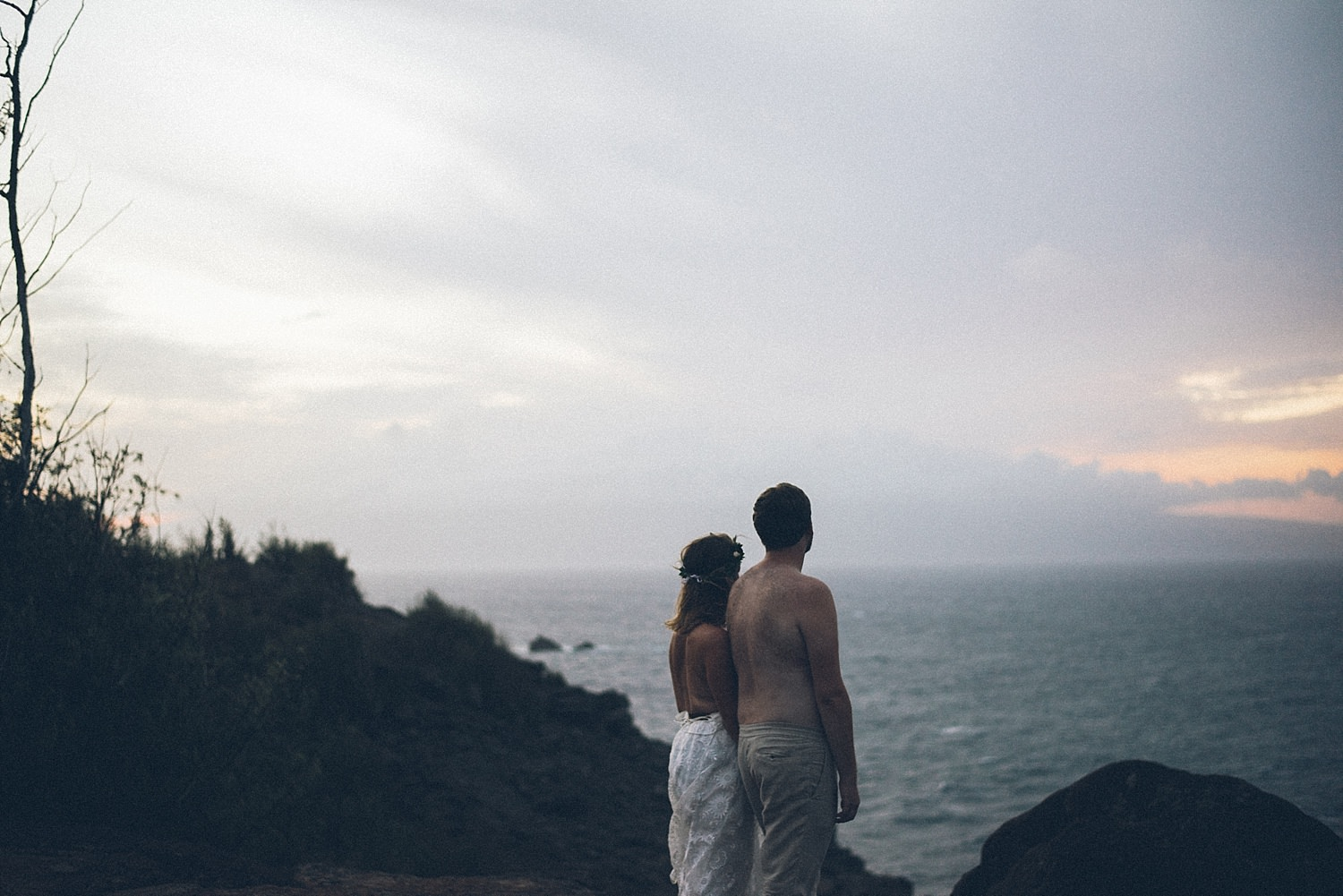 bride and groom shirtless looking out at the ocean