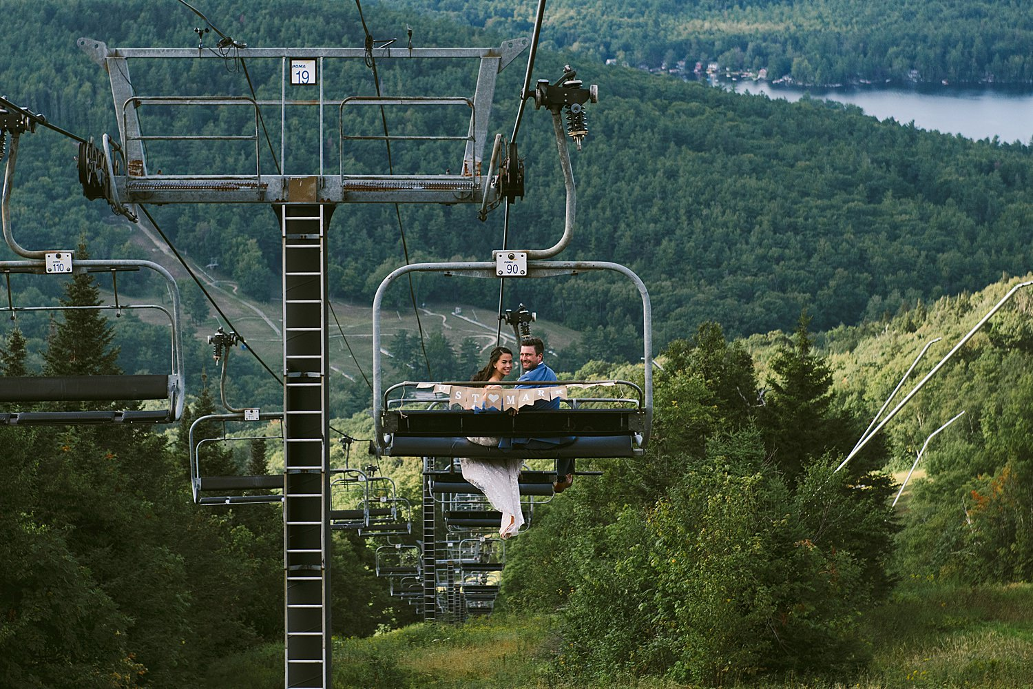 Bride and groom on the chair lift with view of the lake below