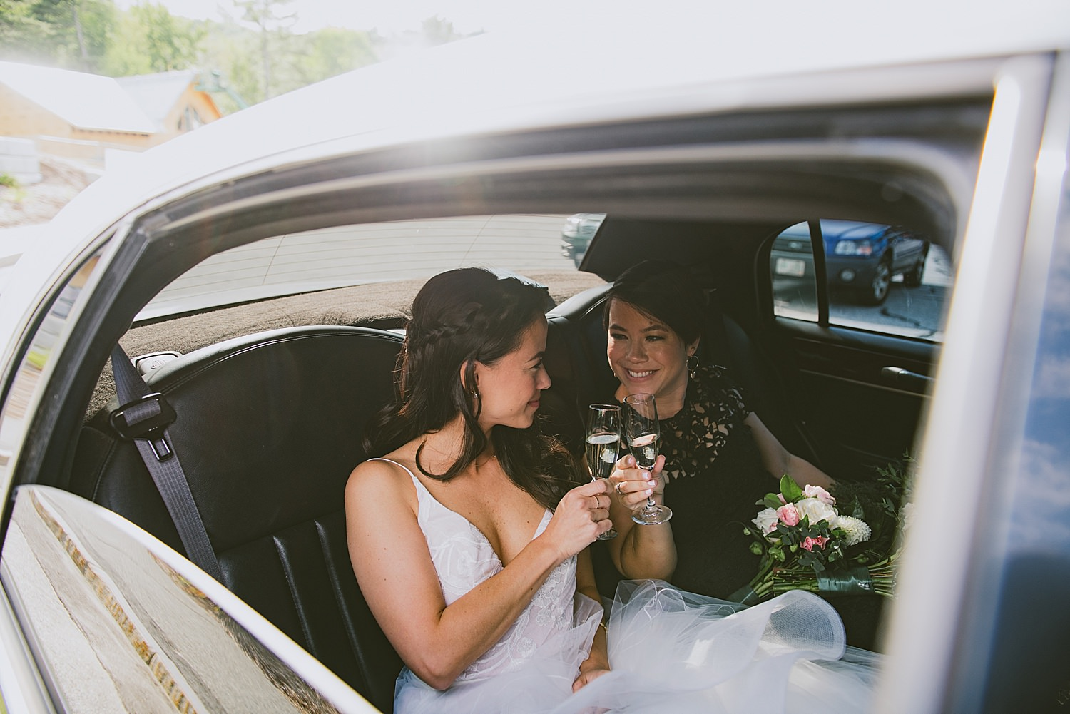 bride and sister toasting in the limo