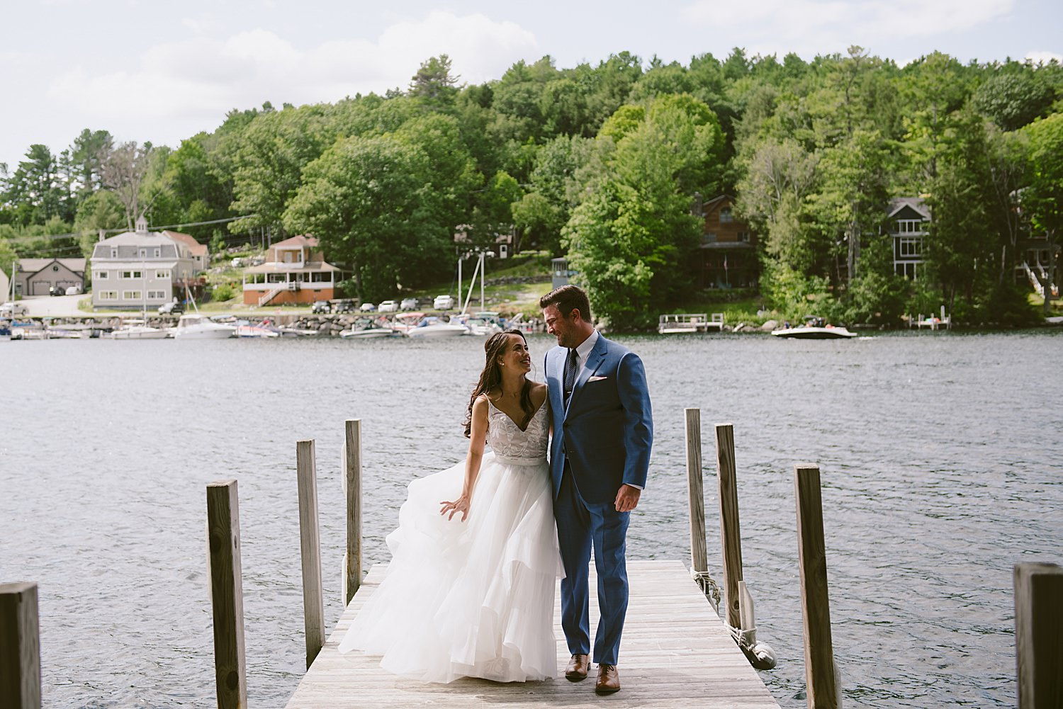 Bride and groom walking along a pier