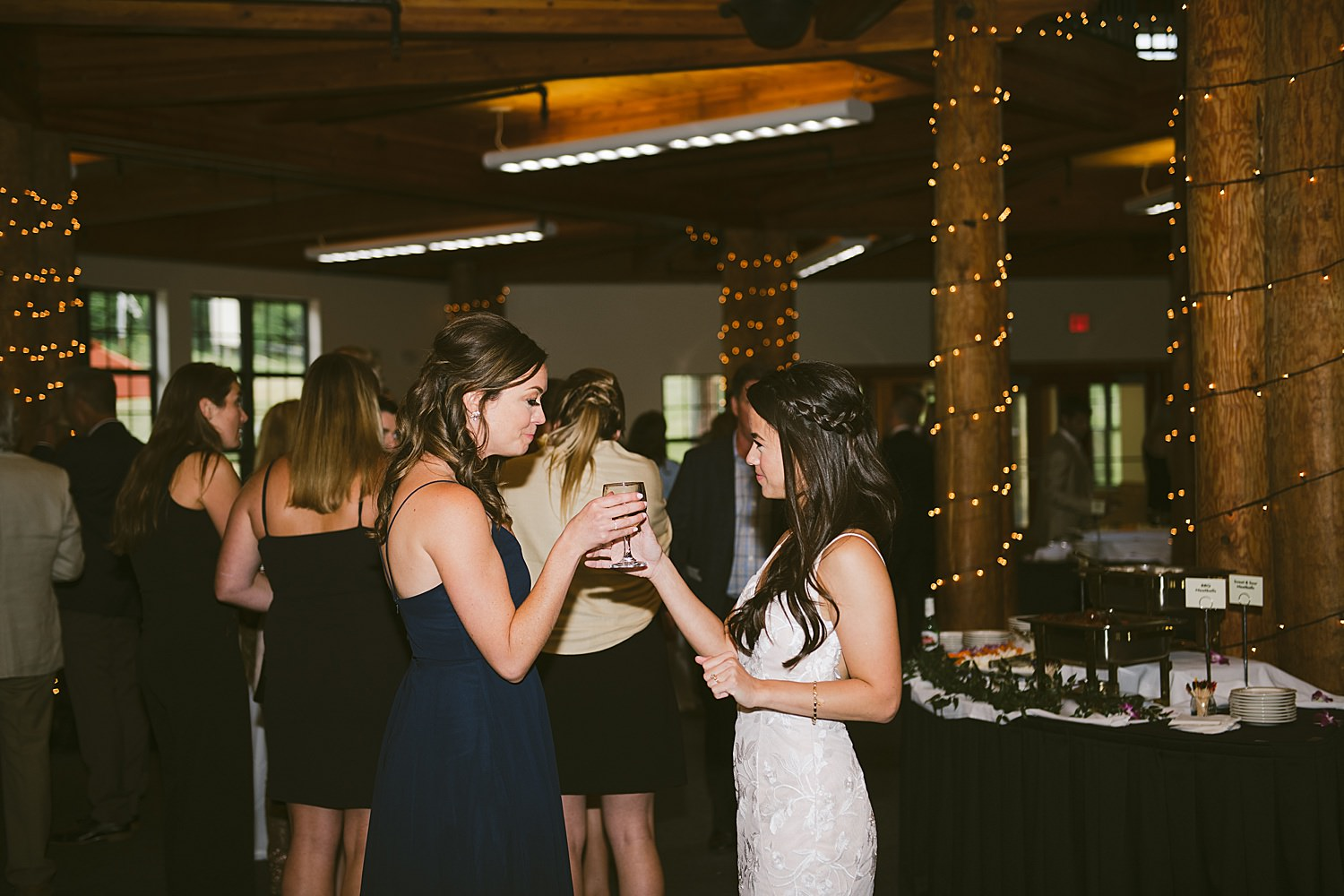 bride and brides maid clinking glasses