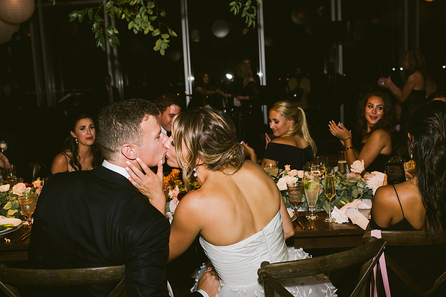 bride and groom at the table kissing
