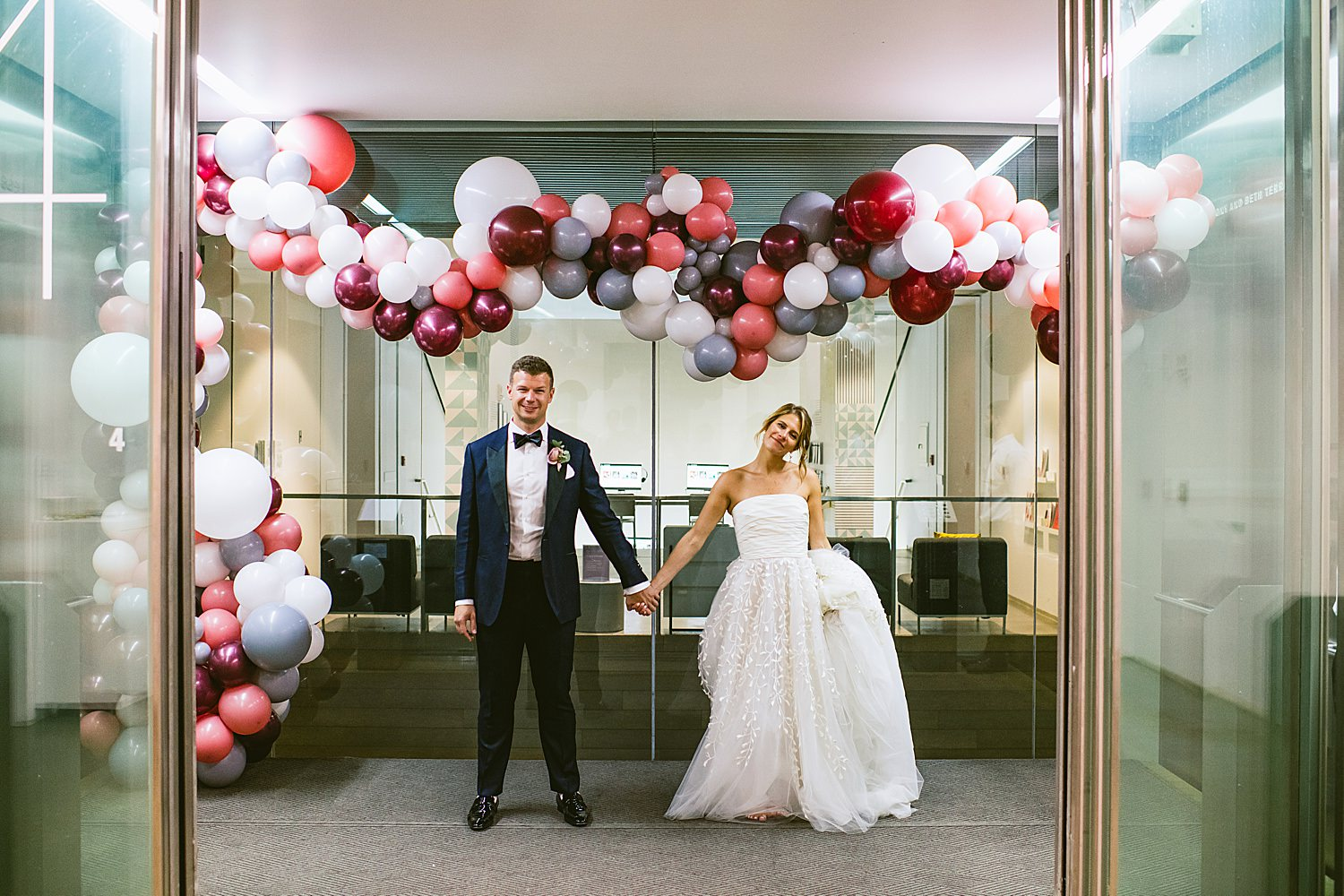 bride and groom in balloon filled elevator