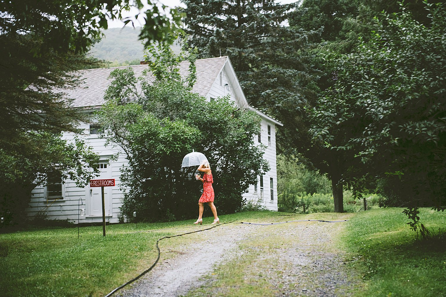 Wedding Guest with umbrella avoiding the rain