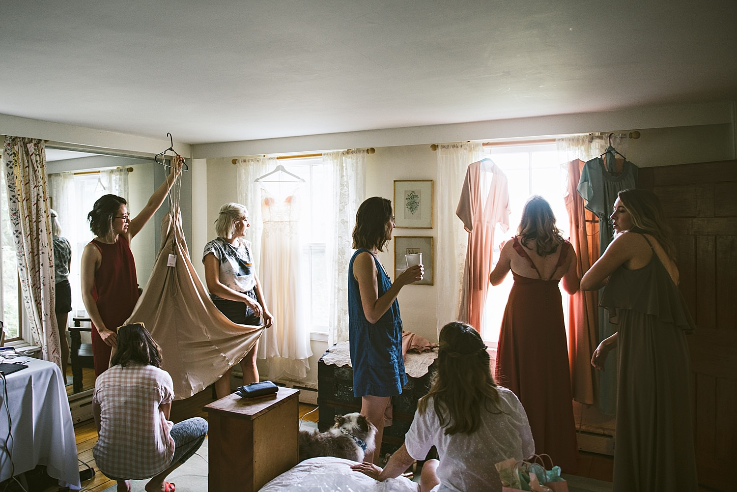 Bride getting ready in a room with all of her bridesmaids