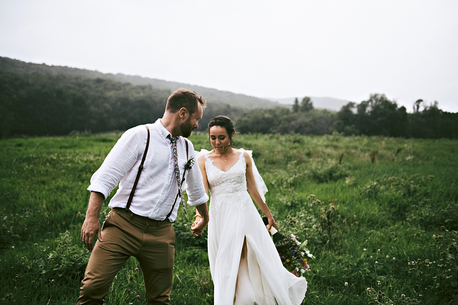 Bride and groom embracing in the rainy field
