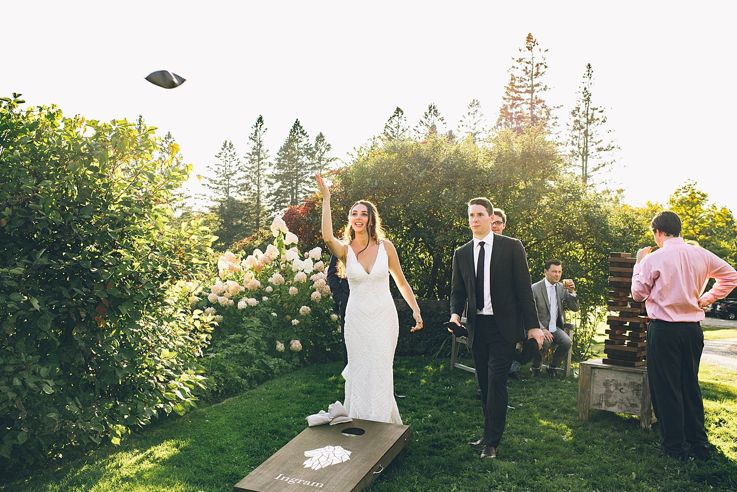 bride and groom playing corn hole