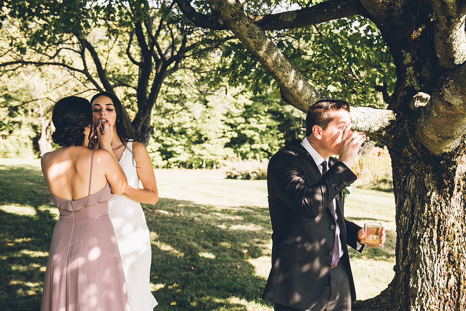 bride getting lipstick on while groom sips her drink
