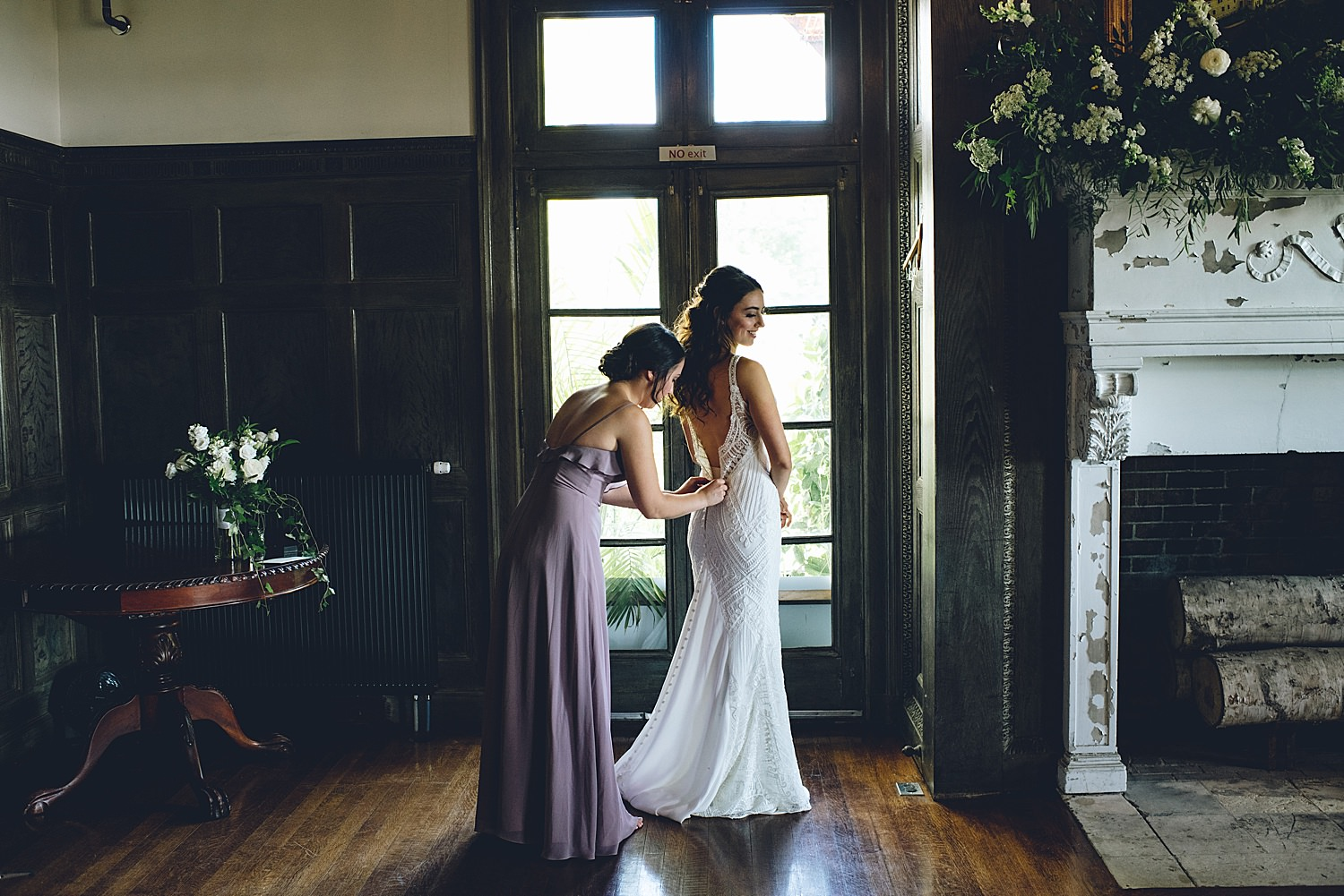 bride getting wedding dress on with sisters help