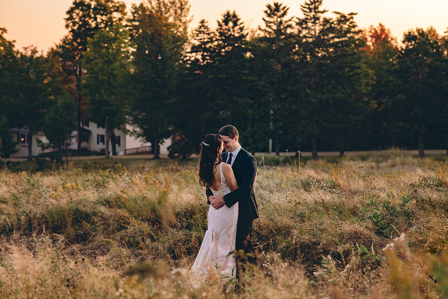 bride and groom embraced at sunset